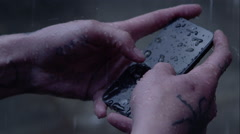 Rain pours down onto a smartphone while hands try to write a txt message. Stock Footage