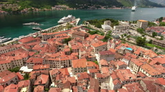 Red roofs of medieval old town of Kotor and urban port with ships. Montenegro Stock Footage