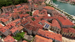 Hovering over red roofs of old town of Kotor city, central part with bell tower  Stock Footage