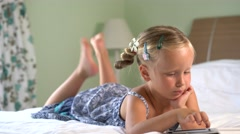 Four-year girl plays a game on the tablet Stock Footage