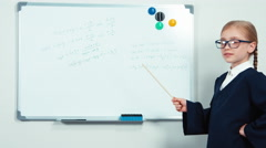 Little student holding pointer standing near whiteboard - stock footage