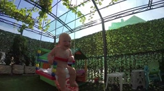 Seven-month toddler for the first time on a swing, slow motion Stock Footage
