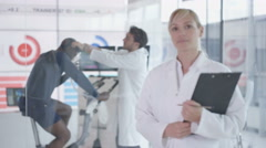 4K Portrait of sport scientist in hi tec lab, man being tested in background Stock Footage