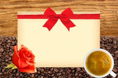 Postcard with red bow on roasted coffee beans, white cup and wooden backgroun Stock Photos