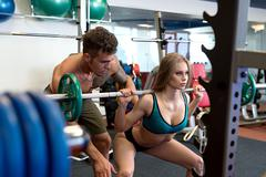 At gym. Sexy coach helps girl to do squat Kuvituskuvat