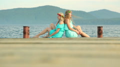 Cute girls with wreaths on their heads are resting on the river. Two young Stock Footage