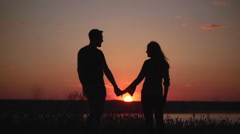 Silhouettes of young couple at sunset. Slow motion Stock Footage