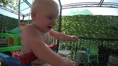 Seven-month toddler for the first time on a swing enjoying open heartledly Stock Footage