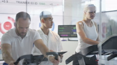 4K Man & woman on fitness machines being tested & monitored by sports scientist Stock Footage