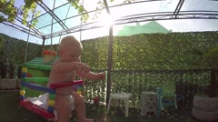 Seven-month toddler for the first time enjoys swinging Stock Footage