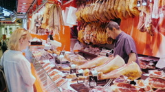 Barcelona, Spain - Woman buys the ham on the market. The counter Stock Footage