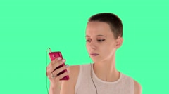 Beautiful bald girl, with short hair brunette on the green screen, listening to - stock footage