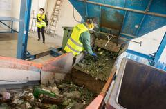 Worker is sorting the recyclable glass material and removing non recyclable t Stock Photos