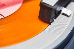 headshell of turntable on orange vinyl - stock photo