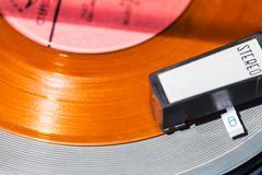 above view of headshell on orange vinyl record - stock photo