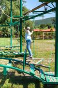 Girl overcomes an outdoor obstacle course Stock Photos