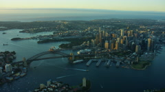 Aerial view at sunrise of Sydney Harbour Bridge and downtown city buildings Stock Footage