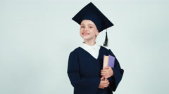 Portrait graduate girl 7-8 years in the mantle and hat entering at frame - stock footage