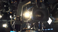 Camera hangs on ceiling and spotlight shines in television studio Stock Footage