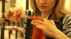 Female hairdresser trims a red hair Stock Footage