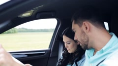 Happy couple with map discussing route in car  Stock Footage