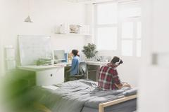 Young adults studying in apartment - stock photo