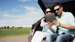 Happy couple with tablet pc at hatchback car trunk  Stock Footage