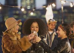 Young women toasting champagne glasses at nighttime rooftop party Kuvituskuvat