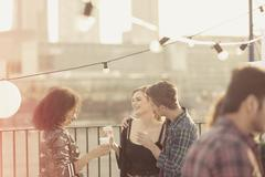 Young adult friends talking and drinking at rooftop party - stock photo