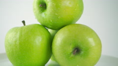 Close up 4K ProRes dolly shot of green apples and pouring water. White - stock footage