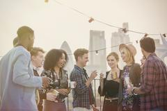 Young adult friends drinking and enjoying rooftop party Stock Photos