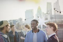 Young men talking at rooftop party Stock Photos