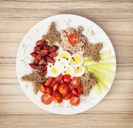 Sliced whole wheat bread with butter, tuna, sausage, cherry tomatoes, paprika - stock photo