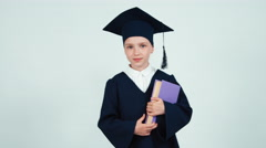 Portrait graduate girl 7-8 years in the mantle and hat holding her book Stock Footage