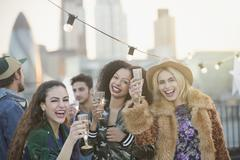 Portrait enthusiastic young women drinking champagne at rooftop party Stock Photos