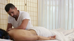 Male massage therapist treat female patient - stock footage