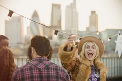 Portrait enthusiastic young woman drinking champagne at rooftop party - stock photo