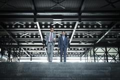 Corporate businessmen with coffee descending modern stairs Stock Photos