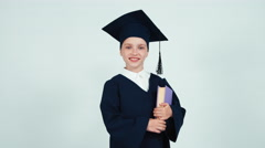 Portrait graduate girl 7-8 years in the mantle and hat turns around at camera Stock Footage