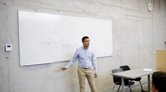 Teacher or lecturer at white board in lecture hall Stock Footage