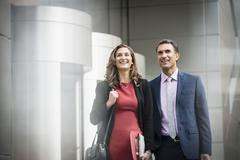 Smiling corporate businessman and businesswoman outside building - stock photo