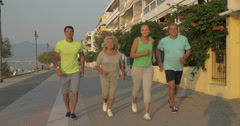 Young and senior people jogging at sunset Stock Footage