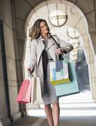 Businesswoman with shopping bags checking wristwatch in cloister - stock photo