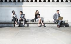 Corporate business people working on sunny bench outdoors - stock photo