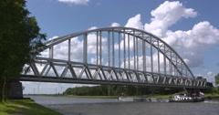 Inland ship Saturnus under arch rail bridge across the Amsterdam-Rhine canal Stock Footage