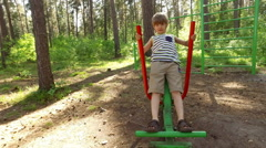 Young Boy training on a playground equipment outdoors Stock Footage