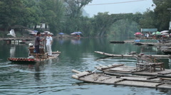 Bamboo raft on Yulong river with ancient stone arch bridge Stock Footage