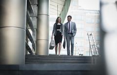 Corporate businessman and businesswoman descending stairs outdoors Stock Photos