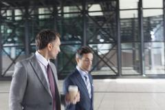 Corporate businessmen with coffee walking and talking outside building Stock Photos