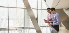 Corporate businessmen using digital tablet at railing in office Stock Photos
